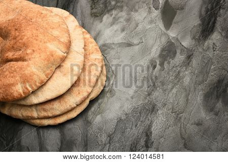 Pita bread loaves on dark gray slate with copy space.
