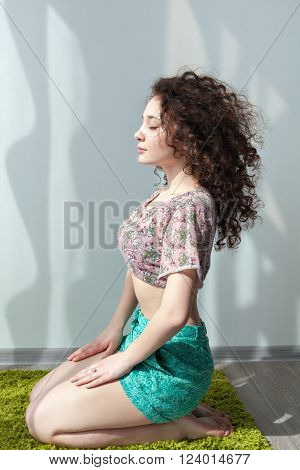 Young girl with curly hair sitting on the floor, on a green rug, do stretching exercises. Meditation. Practice yoga at home. Enjoy life. Doing exercises in the morning in the bright sun room.