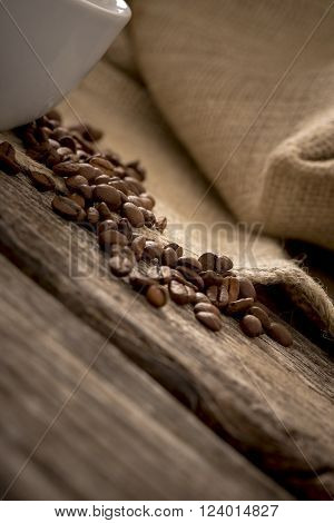 Closeup view of coffee beans scattered on rustic textured wooden desk with burlap sac in background and part of white coffee mug on the left side of the image.