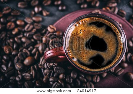 Coffee. Cup of black coffee and spilled coffee beans. Coffee break.