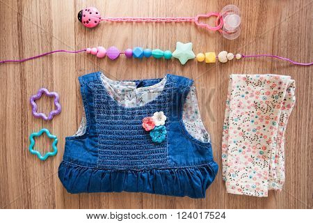 Top view of jeans girl's dress decorated with red blue white flovers beige girl's panties with blue brown red flovers pattern and colored silicone beads and pink nipple with pink ladybird nipple holder and blue and violet plastic stars on wood background