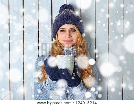 Winter portrait of young beautiful blond woman in her knitted warm clothing, with cup of hot drink. Snowy effect