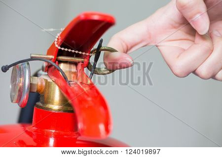 Close- up Fire extinguisher and pulling pin on red tank.