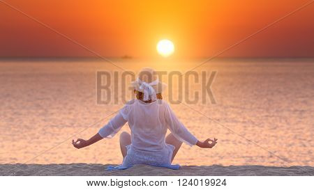 Woman in retro hat meditating and relaxing in yoga pose towards the sun at peaceful beach sunset during your holiday on Greek coast of Aegean sea.