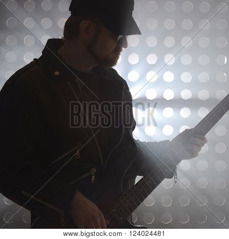 Bassist playing bass guitar in smoke. backlight