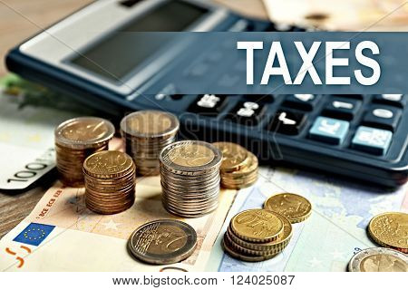 Tax Concept. Black calculator with banknotes and coins, close up