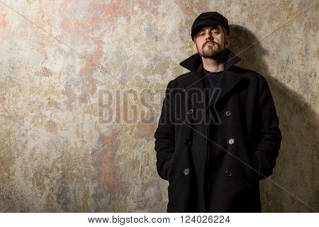 Cool guy rocks coat and newsboy cap as he takes a moment to think