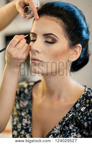Makeup session with beautiful young brunette woman. Makeup artist doing the eyebrows of an attractive dark hair lady. Makeup artist hand applying dry cosmetic tonal foundation on a face using brush.