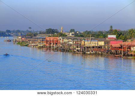 Traditional Riverside village and boat near Bangkok Thailand
