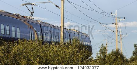 Blue train passes by on a railroad. Electrical lines in the air. Evening sunshine, bushy this side.