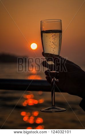 Orange glowing sun setting behind a glass of champagne held up to the light with bubbles rising through reflected light