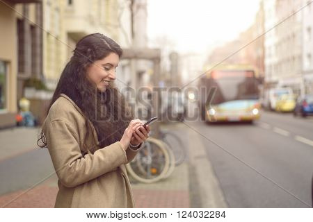 Texting brunette woman reads a message on her mobile phone and smiles while being unaware of approaching bus