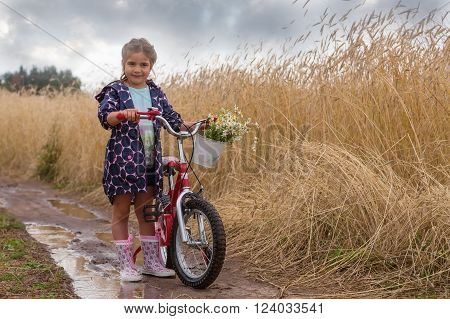 girl to stand in the field with bicycle in a big pool