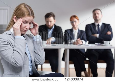 Stressed young woman before job interview and three bossy employers waiting for her