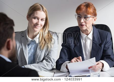 Two businesswomen in corporation talking with new male applicant during job interview