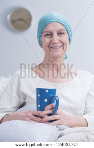 Older smiling positive woman with scarf on head after chemotherapy relaxing at home with cup of tea