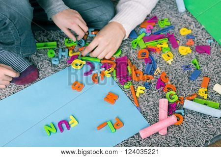 Close-up of boy disposing colorful letters on blue plate during language lessons