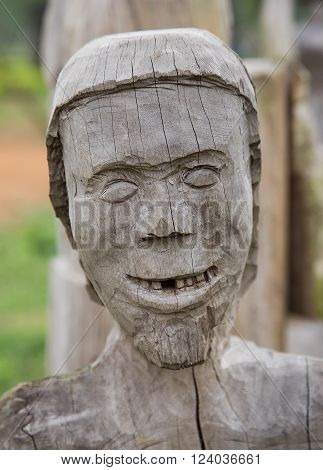 Wooden face smiling, close up. Statue of human character of minority group.