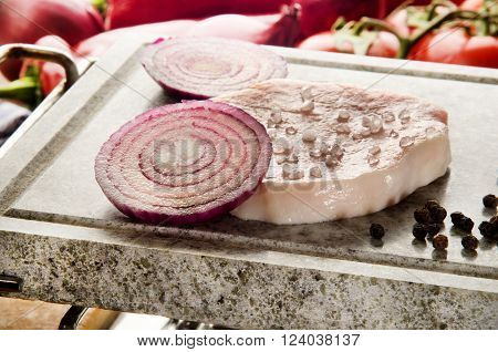 boneless pork chop with coarse salt and purple onion slice on natural marble grill hot stone