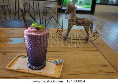 Fresh and healthy blueberry smoothie frappe in glass and wooden tray and table with craving wooden horse toy as decoration in evening / Fresh and healthy blueberry smoothie frappe