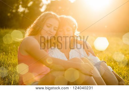 Mature mother with her teenage daughter sitting on grass and sharing happy moments, flare from setting sun in photo