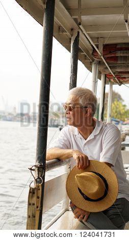Senior Asian man riding a ferry boat to cross Chaopraya river in morning sun
