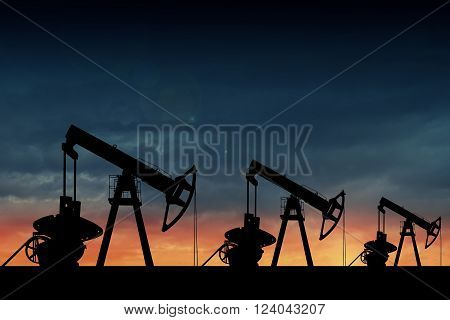 Silhouette of three oil pumps at sunset. Oil field at sunset.