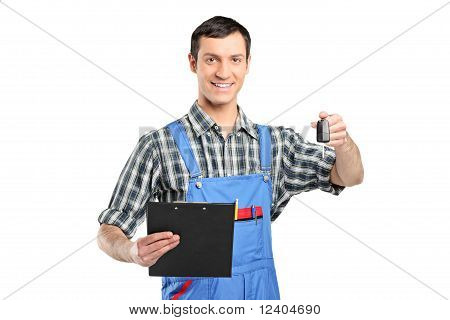 Mechanic In Uniform Holding A Car Key And Clipboard