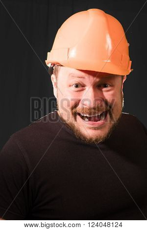 Worker in safety helmet emotional portrait in low key