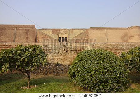 Neatly kept gardens and red brick walls at the restored Bathinda fort in Punjab, India.