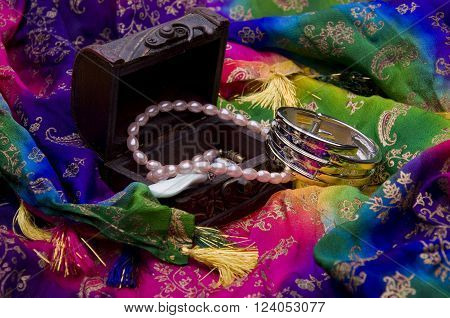 Ancient treasure chest with jewelry on a multi-colored oriental fabric background