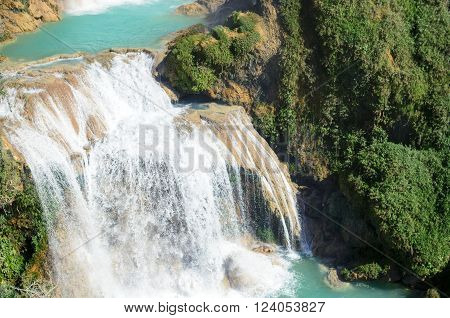Closeup of powerfull waterfall with turquoise pools