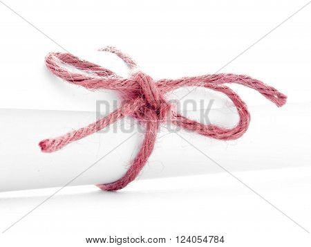 Handmade red string knot tied on white paper roll, isolated