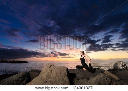Summer sunset yoga session on beautiful Playa Fanabe beach - tropical Tenerife island, Canary in Spain. Eka Pada Rajakapotasana - legged king pigeon pose
