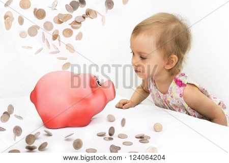 Two-year old girl looks at piggy bank thinking what to buy for savings.