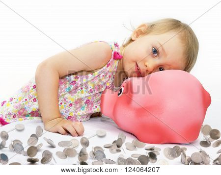 Two-year-girl dreams about what can buy for the money from piggy bank.