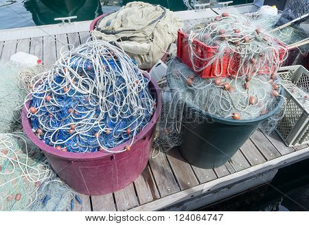 Fishing nets and fishing tackle are on wooden pier