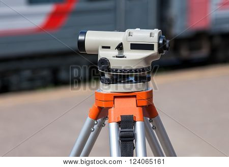 Geodetic equipment optical level mounted on tripod at the railway station