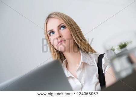 Blonde businesswoman in front of laptop. View from under table. Office at background. Concept of work.