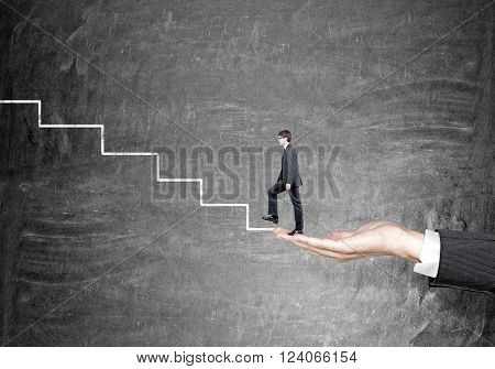 Hand holding businessman starting to climb stairs drawn on black wall. Concept of career growth.