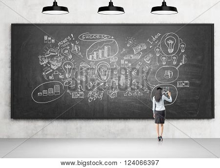 Young businesswoman writing on blackboard business icons on it three lamps above. Back view. Concept of starting business.