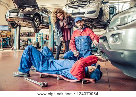Two mechanics fixing a car and speaking with the customer in a workshop - Car at the annual test check-up