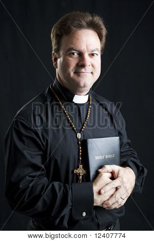 Portrait of a priest with a rosary and a bible.  Dramatic lighting over black background.