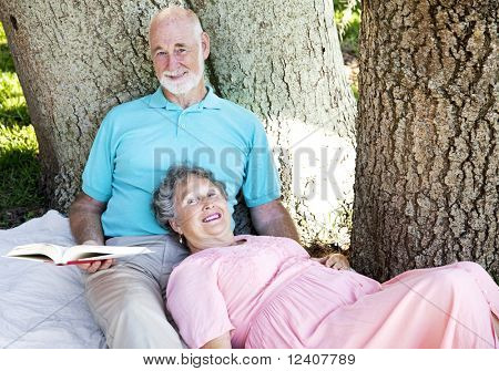 Senior couple reading together outdoors in the park.