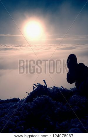 Man legs in big boots laying on the ground in a frozen grass, resting on a hill. Tired hiker and watching into misty daybreak. Autumn misty day in mountains.