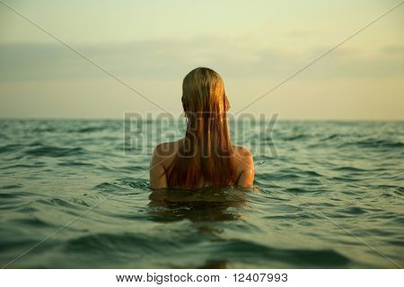 The girl swiming in sea waves. An art photo. A beautiful landscape.