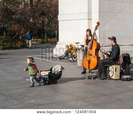 Manhattan New York - December 06 2015: Child left some money to street musicians playing during lazy Sunday afternoon in Washington Square Park.