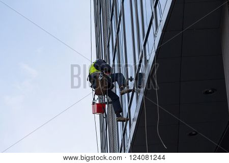 Industrial climber washes the facade of a multistory building. Industry