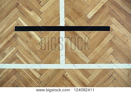 Black and white lines in playground. Worn out brown wooden floor of sports hall with colorful marking lines.