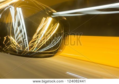Motoring abstract Rear vision mirror travelling through tnnel picks up lights of other cars in golden hues Victoria Tunnel Wellington